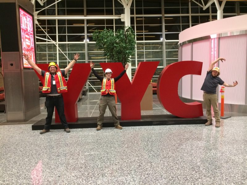 Three men posing in front of a large 3D sign