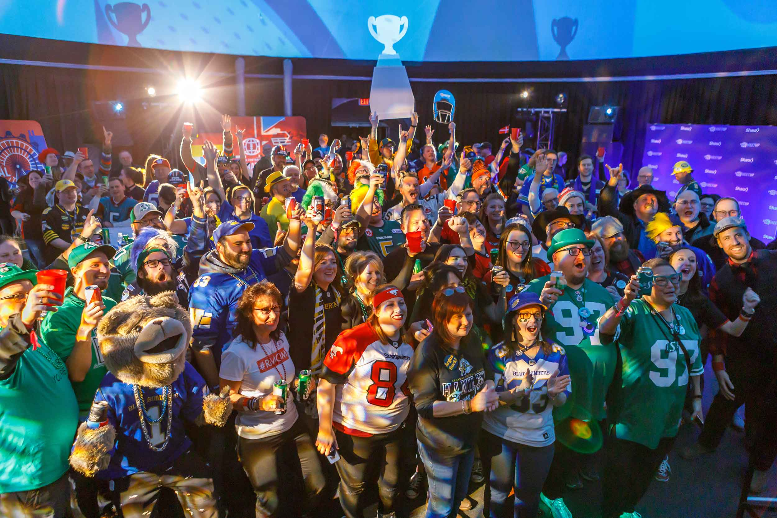 Crowd dressed in assorted jerseys watching a screen